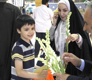 اهداء گل به بازدیدکنندگان نمایشگاه قرآن در شب ولادت امام حسن مجتبی (ع)